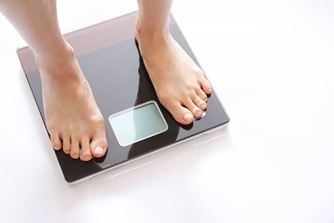 食欲不振による体重減少を実際に体重計で確認している写真