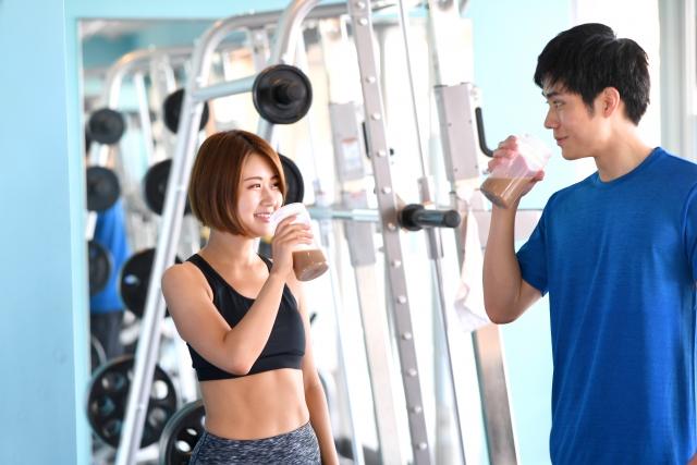 プロテインを飲む男性トレーナーと女性会員