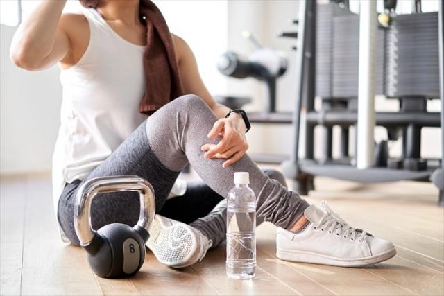 トレーニングで汗をかいて休憩する女性