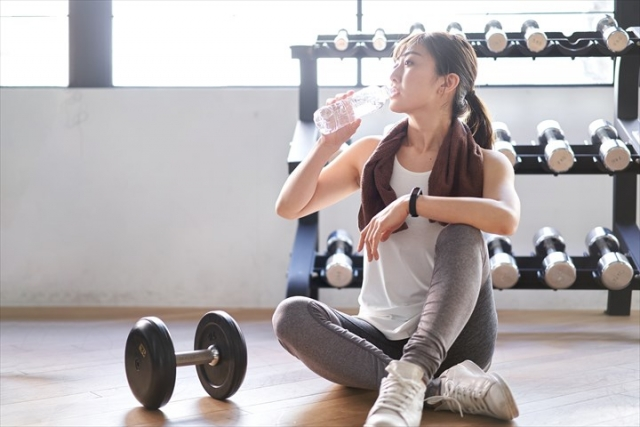 ダンベルエクササイズで汗をかいて水分補給をする女性