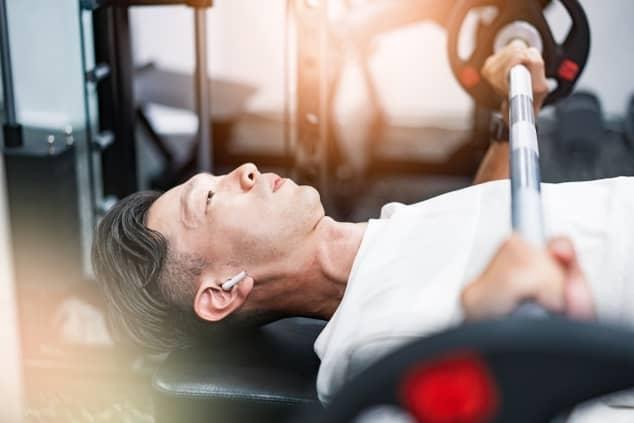 ジムのトレーニングマシンで筋トレしている男性