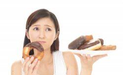 ドーナツの誘惑と戦うダイエット中の女性